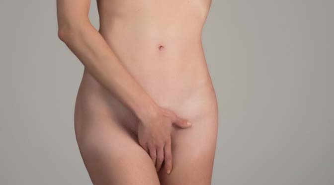 woman holding her hands over her vagina